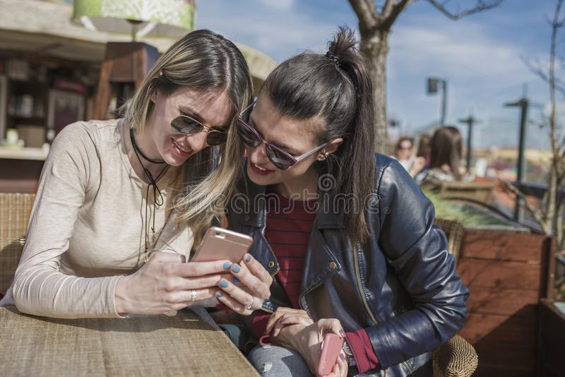 Two beautiful young women having fun outdoors while using their smartphones royalty free stock image