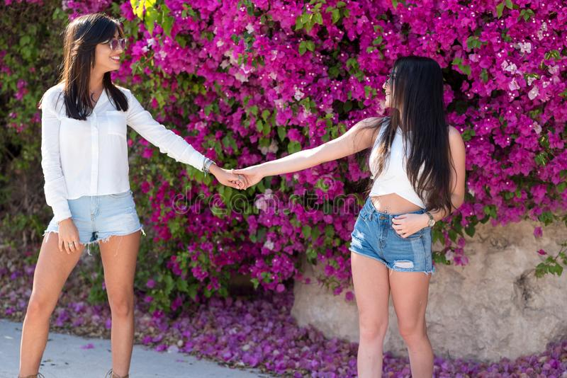 Beautiful happy young women holding hands on colorful natural background of bright pink flowers. Two beautiful young women holding hands having fun in summer royalty free stock images
