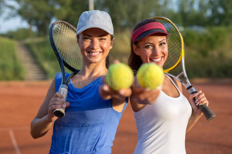 Two beautiful young women holding tennis equipment into the camera royalty free stock image