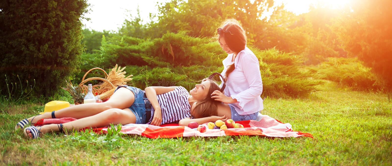 Two beautiful young women on a picnic listening to music on headphones stock images