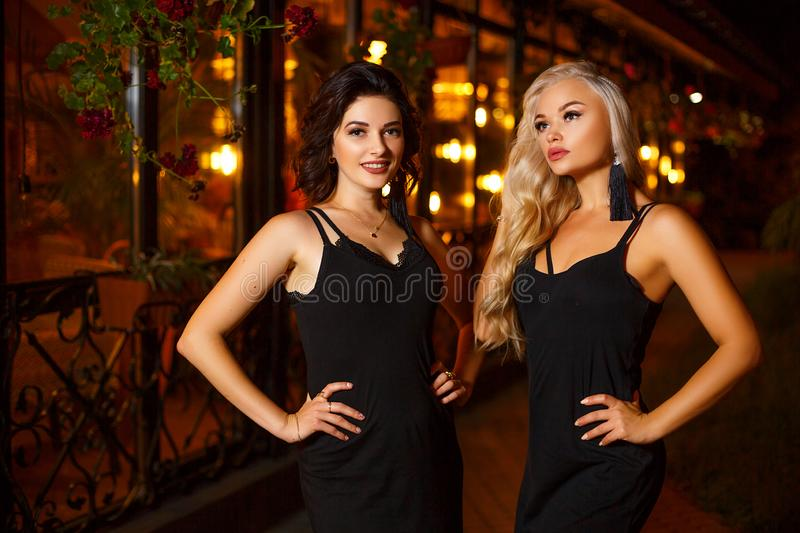 Two beautiful young women posing on camera in the lights of the night city, the concept of beauty and fashion stock photography