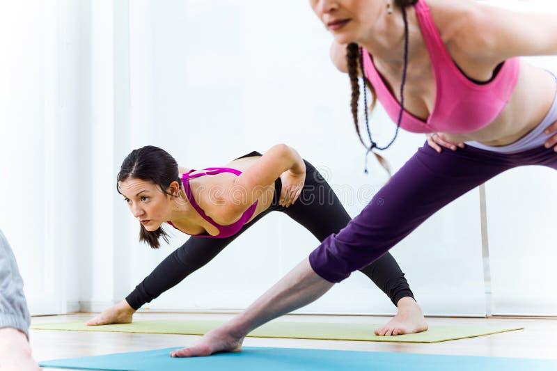 Two beautiful young women practicing yoga at home. Prasarita Pad royalty free stock images