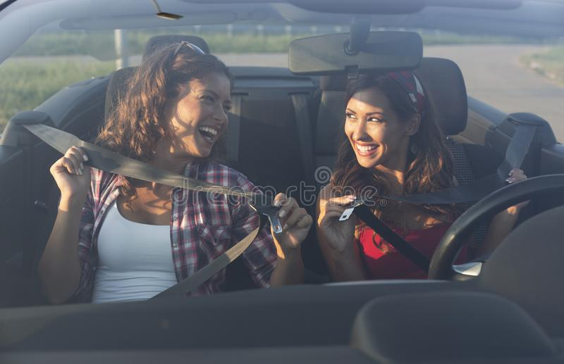 Two beautiful young women putting on seatbelt while smiling royalty free stock images