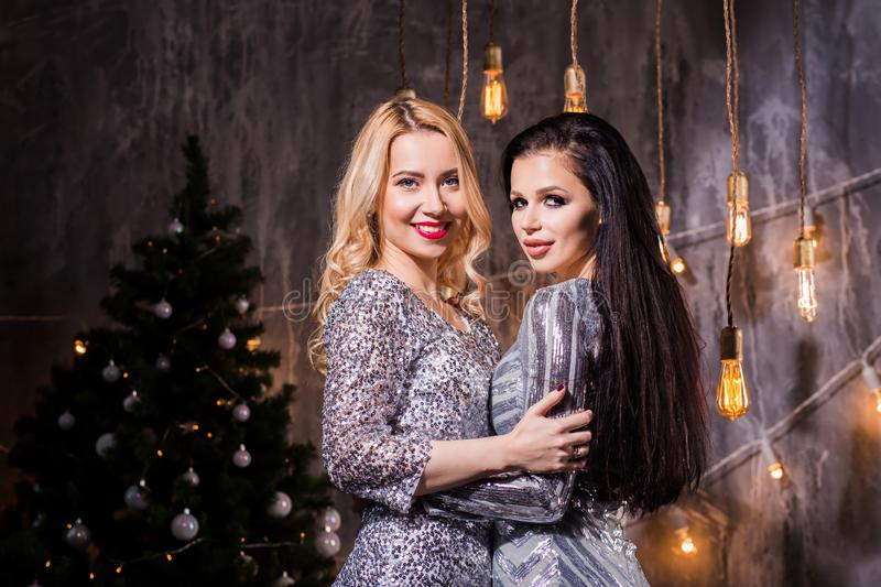 Two beautiful young women in sparkly dresses hugging and looking at camera. Holidays, celebration and people. Concept royalty free stock photos