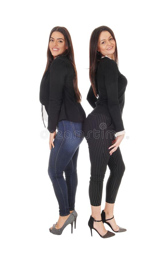 Two lovely woman standing back to back and smiling stock photo