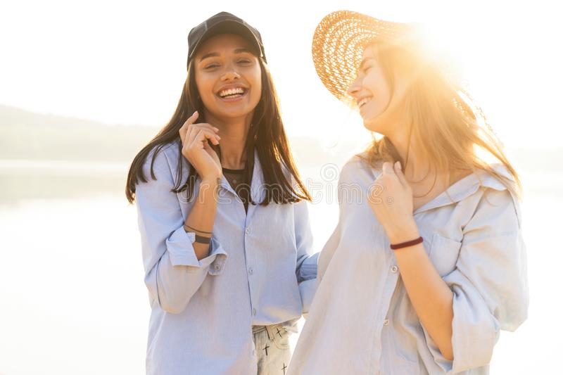 Two beautiful young women strolling on a beach. Female friends walking on the beach and laughing on a summer day. royalty free stock photo