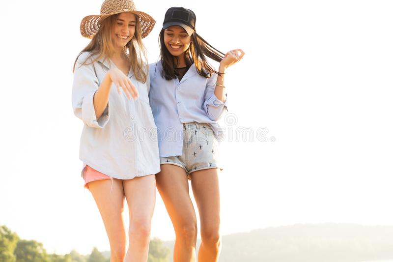 Two beautiful young women strolling on a beach. Female friends walking on the beach and laughing on a summer day. royalty free stock images