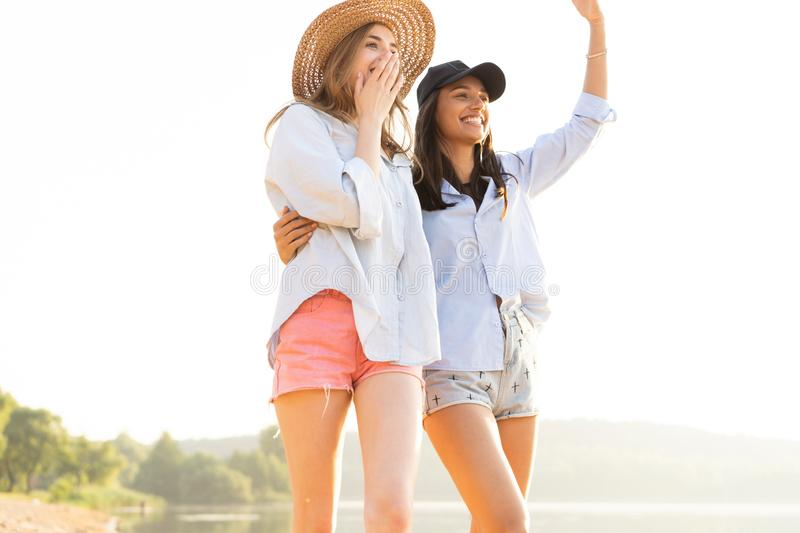 Two beautiful young women strolling on a beach. Female friends walking on the beach and laughing on a summer day. stock images