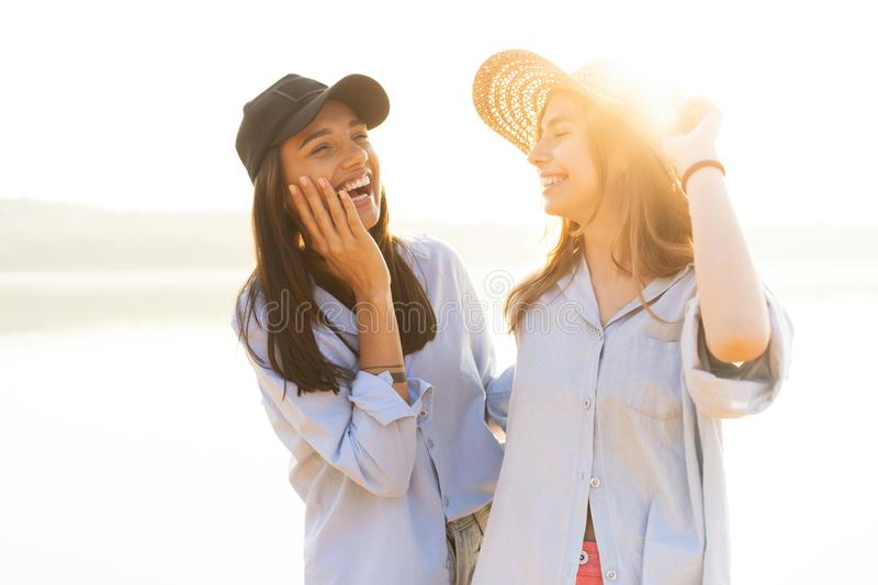Two beautiful young women strolling on a beach. Female friends walking on the beach and laughing on a summer day. royalty free stock image