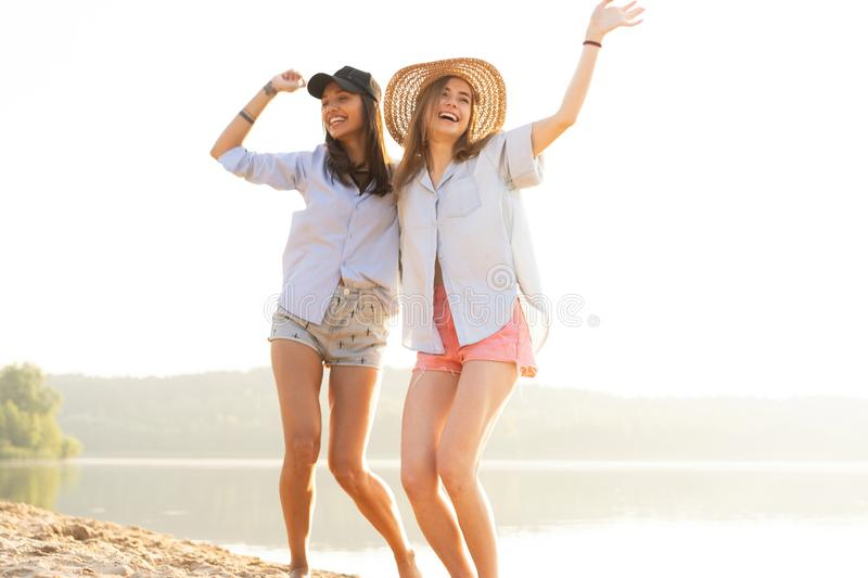 Two beautiful young women strolling on a beach. Female friends walking on the beach and laughing on a summer day. stock photography