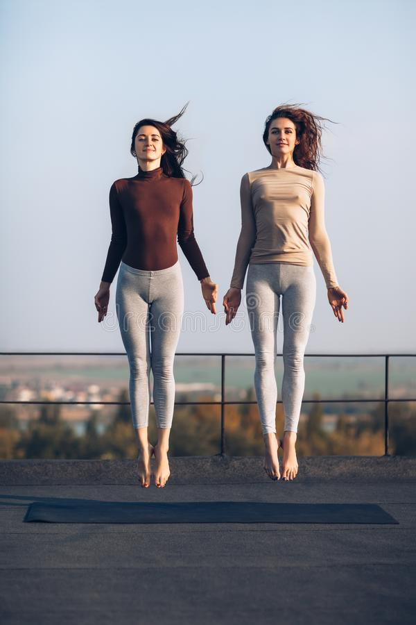 Two beautiful young women synchronously jump on the roof outdoor. S. Girlfriends are engaged in acrobatics and yoga. Frozen jumping women stock photos