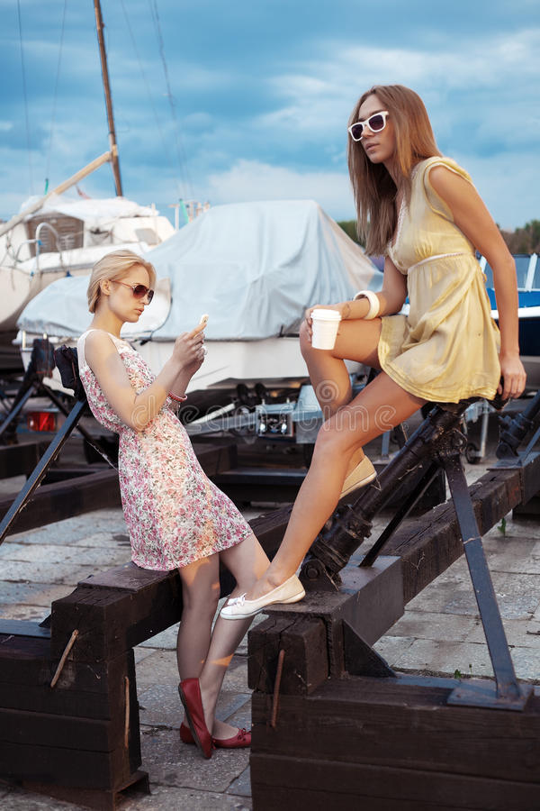Two beautiful young women are talking on pier. Near yachts. Outdoor lifestyle portrait royalty free stock photography