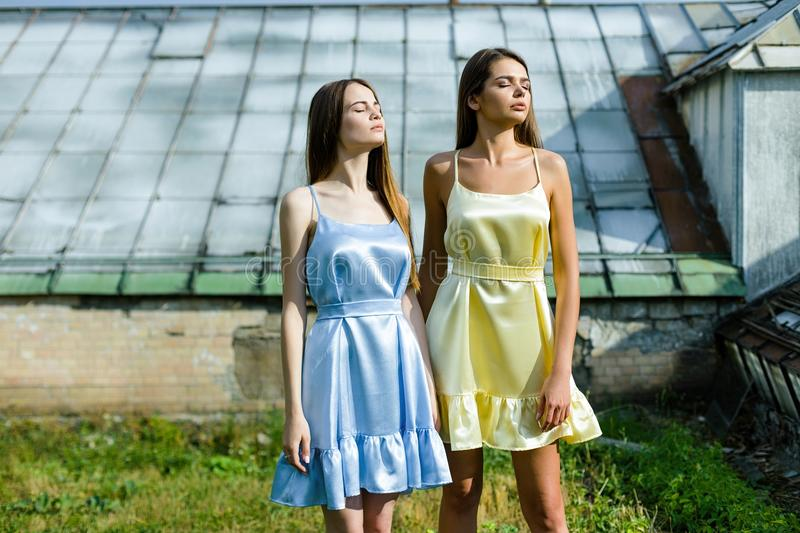 Two beautiful young women. In elegant dresses posing outdoors stock images