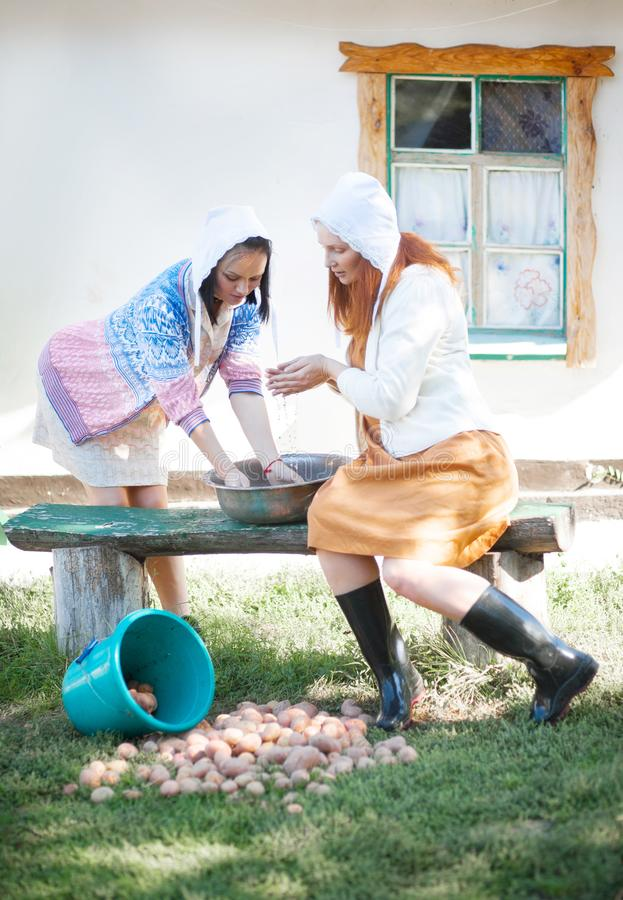 Two beautiful young women washing their hands after agricultural work stock photos