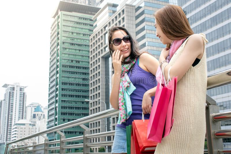 Two beauty women having fun together holding shopping bags royalty free stock photo