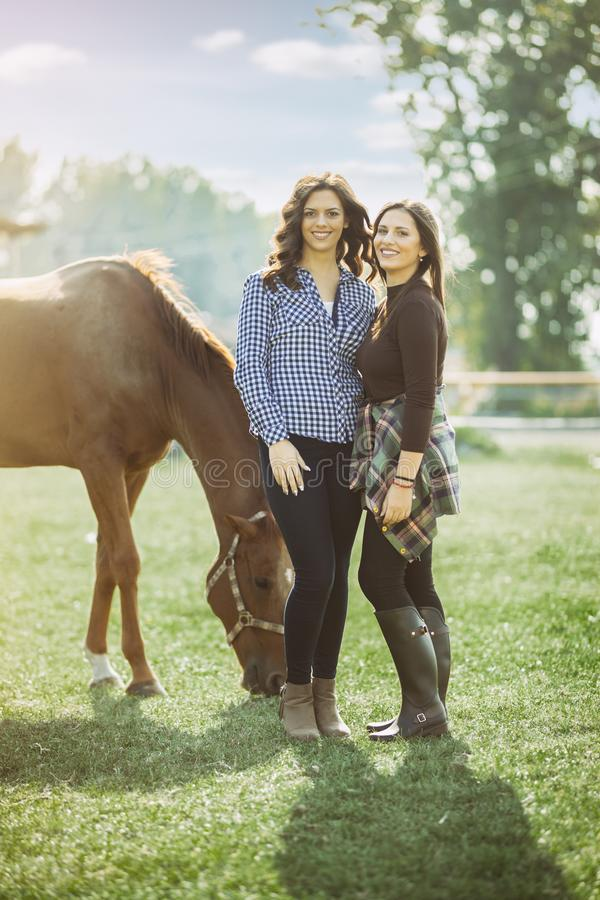 Two woman rider on ranch with horse. Two beauty women rider on ranch with horse royalty free stock photo