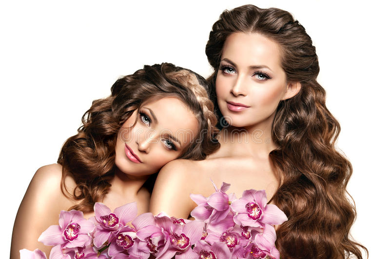 Two beauty young women, luxury long curly hair with orchid flower. Haircut. Beautiful girls fresh healthy skin, makeup, lips, eye stock image