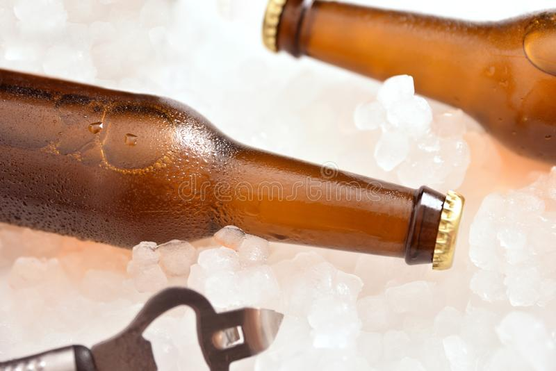 Two beer bottles lying on crushed ice with bottle opener royalty free stock images