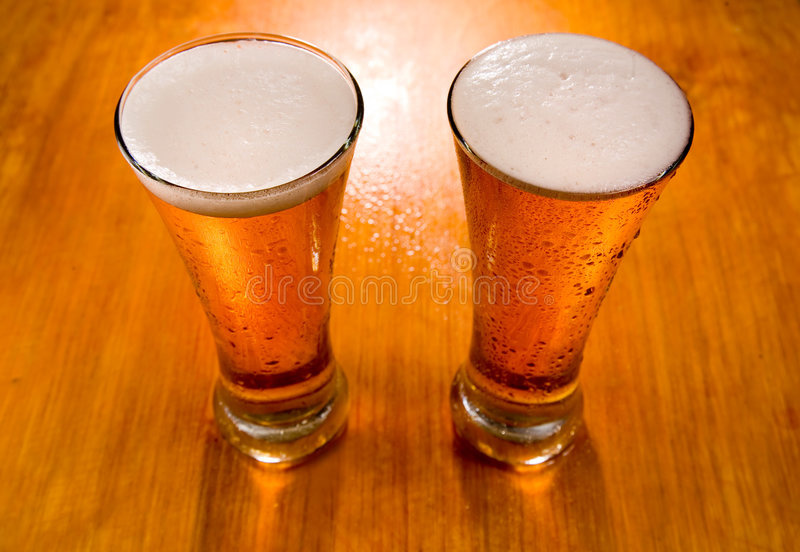 Two beer glasses on wet wooden background stock photography