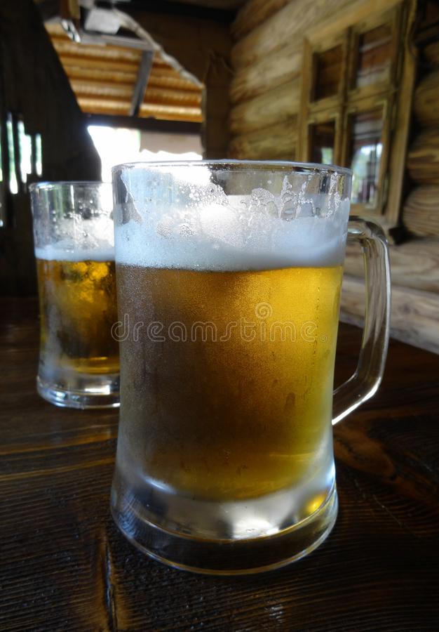 Two beer glasses on the old wooden table at country cottage. Two beer mugs on the table at pub in rural style royalty free stock photo