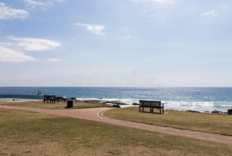 Two Benches on Grass Verge Against Ocean Skyline. Two empty benches on grass verge and paved walkway against ocean skyline and blue sky landscape stock photo