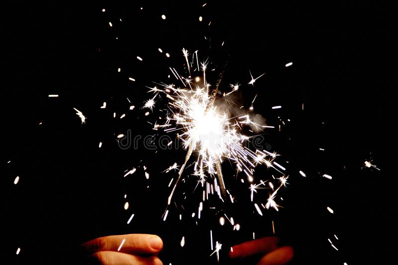 Two Bengal fire in hands sparkles on black background royalty free stock photos