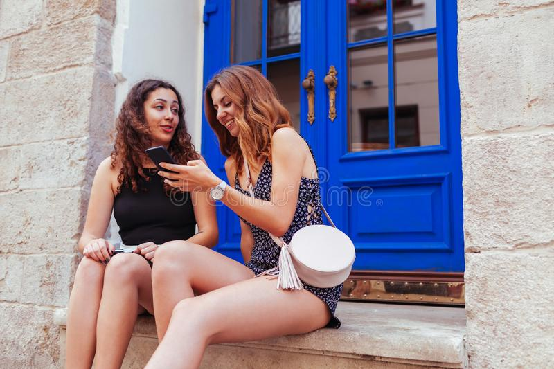 Two best female friends chatting while using smartphone in city. Happy teenager girls talking and laughing. Sitting by cafe window royalty free stock photo