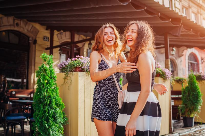 Two best female friends met by cafe in city. Girls laughing and having fun stock photography