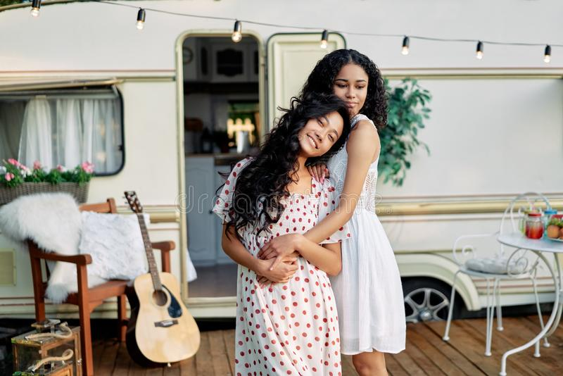 Two best friends embracing outdoors. Asian and afro american woman hugging and have great time together royalty free stock images