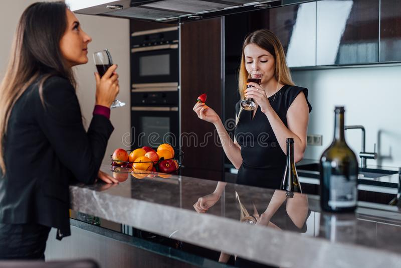 Two best friends having a little house-warming party by drinking red wine standing in the kitchen stock images