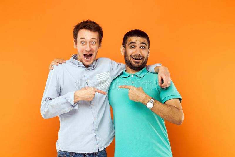 Two best friends hugging, pointing finger each other and looking royalty free stock images