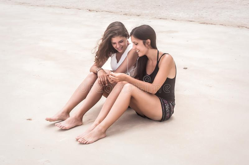 Two best friends listening music on smartphone, enjoying on beach. Tropical travel holidays royalty free stock images