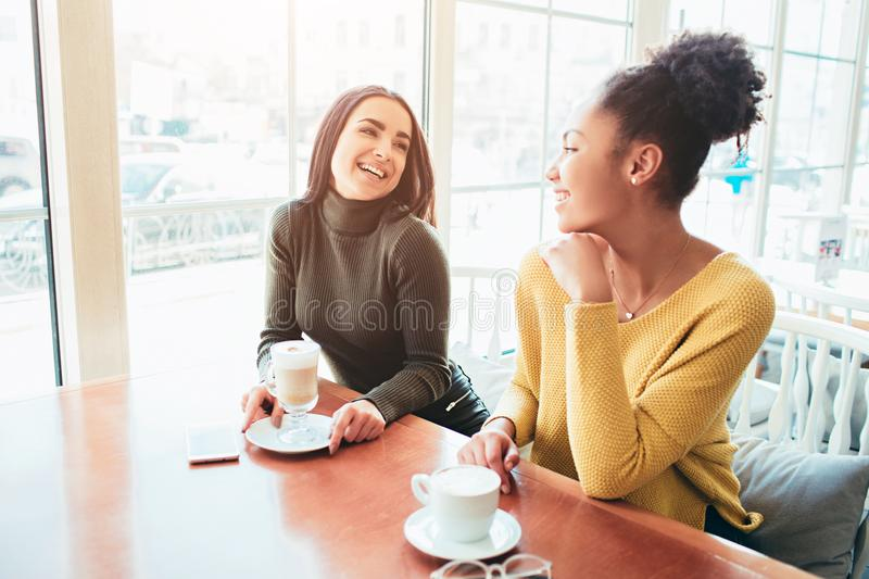 Two best friends are sitting in cafe and spending good time together. Girls are drinking some latte and enjoying their. Conversation. Close up royalty free stock images