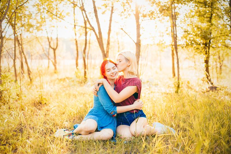 Two best friends spend time in forest. Two young women sitting in forest under daylight. Best friends royalty free stock photo