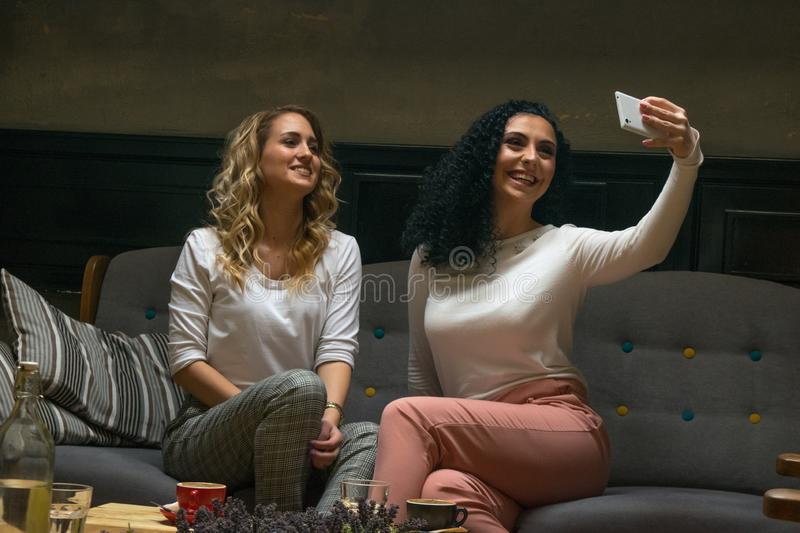 Two best girlfriends are taking selfie in cafe stock image