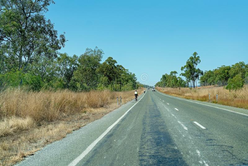 Two Bicycle Riders Traveling On A Country Highway. Two bicycle riders cycling along a country highway with cars coming in either direction stock photography