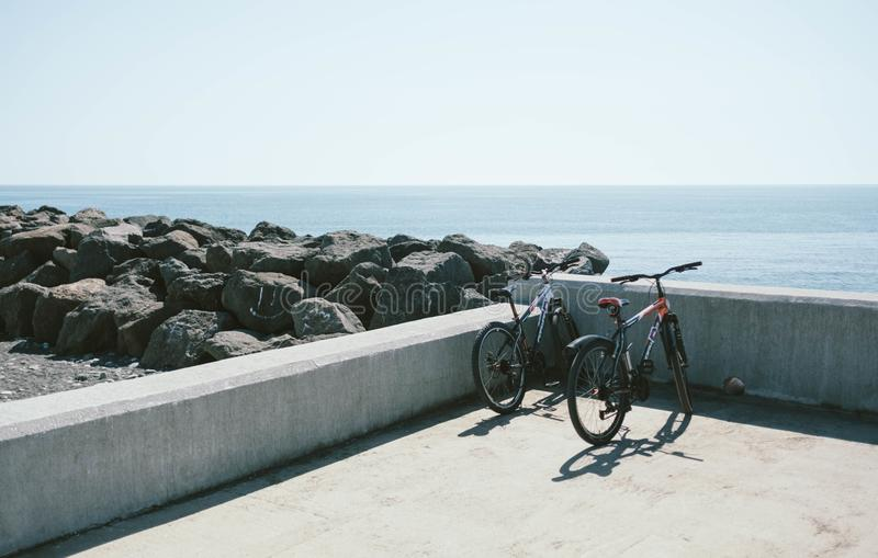 Two Bicycles Behind Gray Concrete Wall royalty free stock images