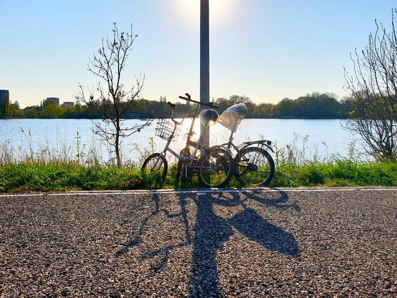Two bicycles parked along the road. With the sun shining in the background stock photography