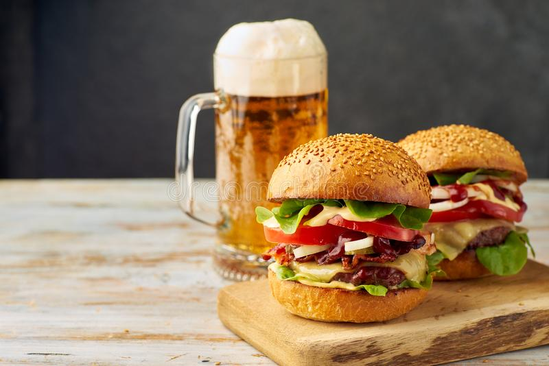 Two big burgers and pint of beer on old wooden table royalty free stock images