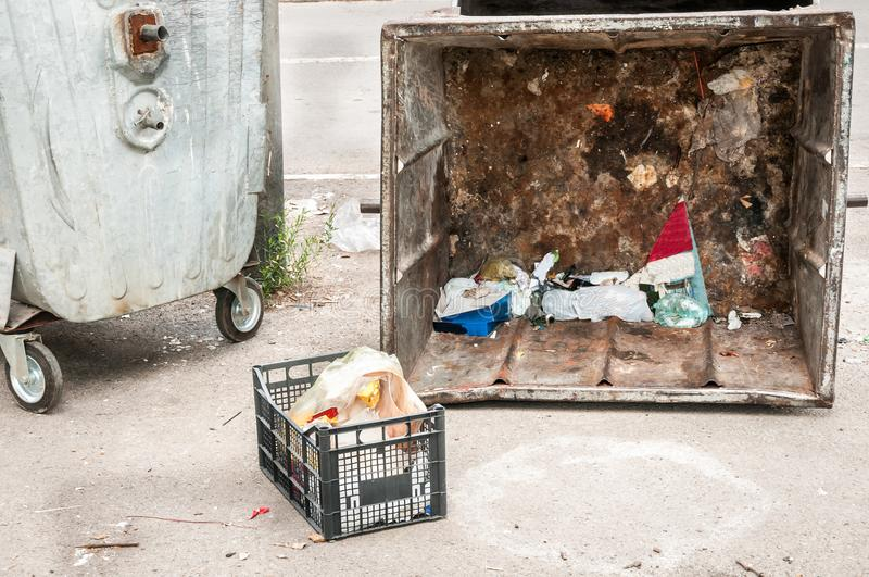 Two big old metal dumpster garbage cans with junk on the street damaged by vandals, vandalism concept.  stock photo