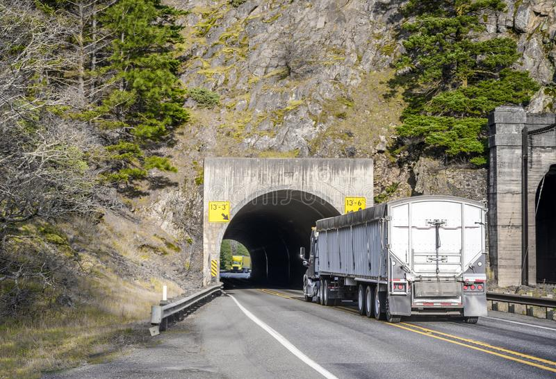 Two big rig commercial long haul semi trucks running in the tunnel towards each other. Two big rig commercial long haul semi trucks transporting cargo in semi stock photos