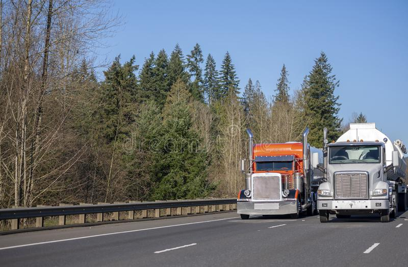 Two big rig orange and white semi trucks with tank semi trailer transporting liquid on the wide road in sunny day royalty free stock photography
