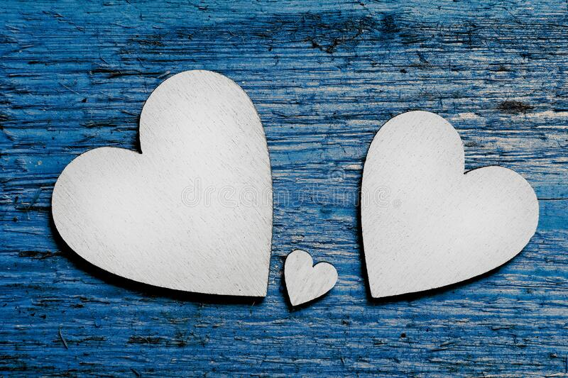 Two big silver wooden hearts and one small heart between them on blue wooden background. Symbol of two parents and one child.  royalty free stock photography