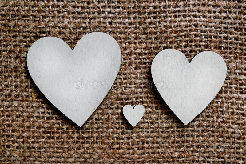 Two big silver wooden hearts and one small heart between them on brown cloth background. Symbol of two parents and one child.  stock photos
