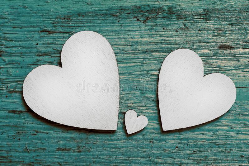 Two big silver hearts and one small heart between them on green wooden background. Symbol of two parents and one child. Two big silver wooden hearts and one stock photos