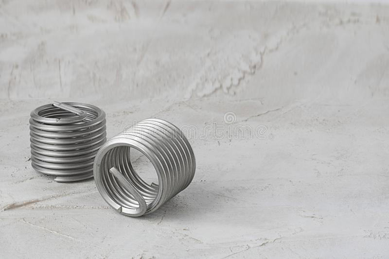 Two big wire thread inserts, grey color, free running on grey cement background. Stainless Steel. Horizontal with copy space for. Text or design stock photography