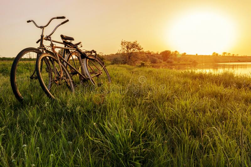 Two bike near the lake sunset background. Two vintage bicycles at sunset. The concept of romance and love stock image