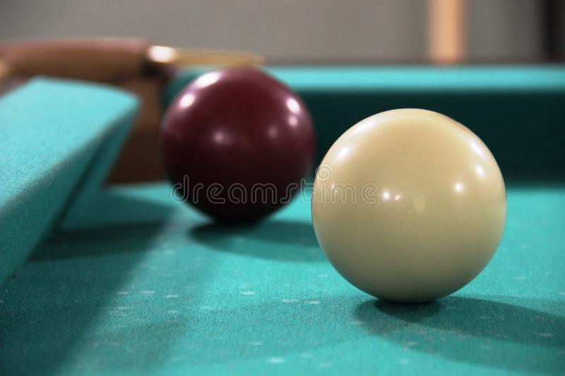 Two billiard balls on green cloth table, cue ball and white ball. framing, russian billiards. Two billiard balls on green cloth table, cue ball and white ball royalty free stock images