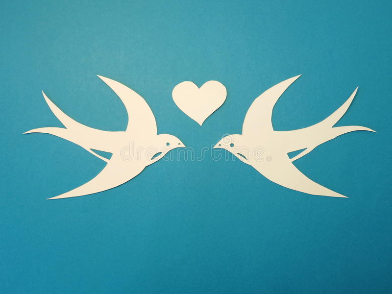 Two birds and heart. Paper cutting. Two birds and heart cut from white paper on blue background royalty free stock photography