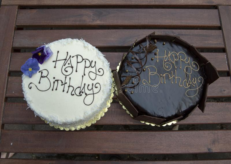 Two birthday cakes, one chocolate and one vanilla. Pictured are two happy birthday cakes, one chocolate and one vanilla. The chocolate cake is surrounded by royalty free stock photography